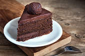 Piece of Chocolate Cake on white plate on wooden background, closeup. Homemade chocolate cake.