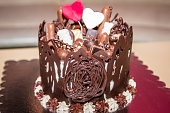 Chocolate birthday cake with small cakes and two hearts on the top