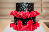 Chocolate birthday cake with red roses and big red ribbon, close up