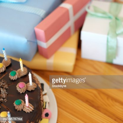 chocolate cake with candle on a table with presents : Stock Photo