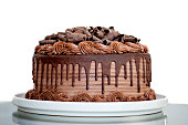 Chocolate Cake with Chocolate Fudge Drizzled Icing and Chocolate Curls on White Backdrop