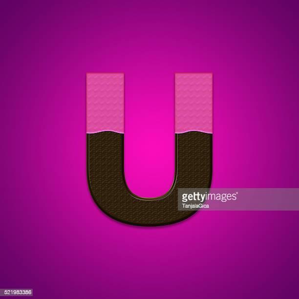 U lettres de bonbons au chocolat isolé sur fond rose