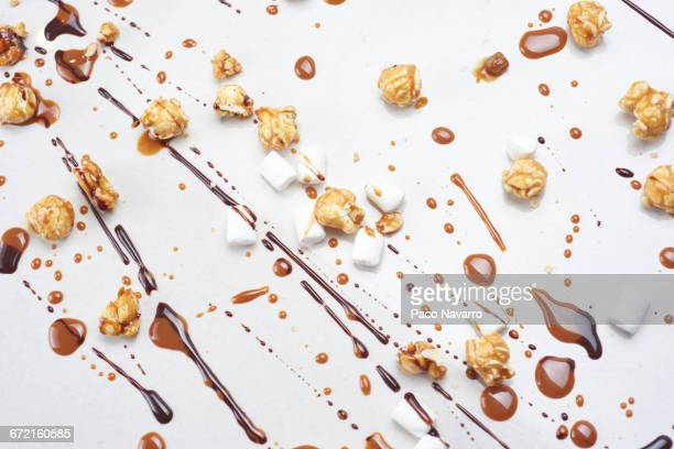 Chocolate, caramel popcorn and marshmallows on white background