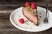 Slice of chocolate cheesecake decorated with pistachios, raspberries and mint leaf on white plate on wooden background.