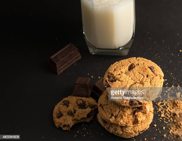 Chocolate chip cookies a glass of milk and chocolates around them Cookies over a black background