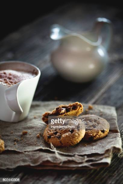 Chocolate chip cookies and cup of coffee on wooden table.