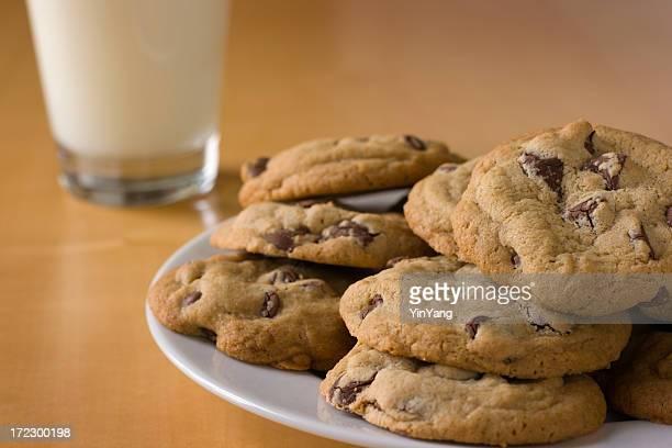 Biscotti con scaglie di cioccolato piatto e un bicchiere di latte su un tavolo