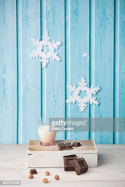 Chocolate cubes, hazelnuts, glass of milk, paper snowflakes on blue wall
