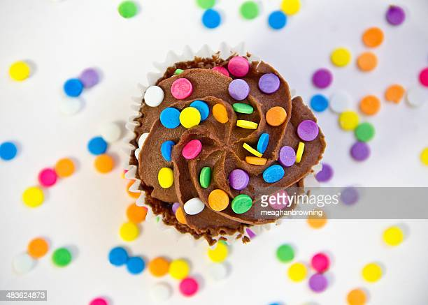 Chocolate cupcake covered with buttercream frosting and multi-colored sprinkles
