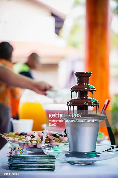Chocolate Fountain On Table Against People