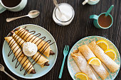 A top down shot of a plate of chocolate hazelnut spread (Nutella) crepes with whipped cream next to another plate of lemon and powdered sugar crepes. Everything is on a weathered dark wooden table wit