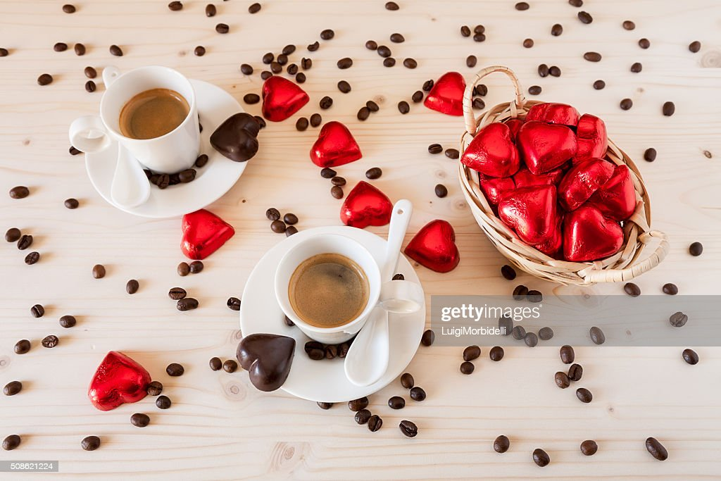Chocolate hearts in a basket and two cups of coffee : Stock Photo