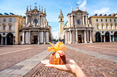 Holding italian chocolate with bow on Turin city background. Turin in Piedmont region in Italy is famous of its chocolate making