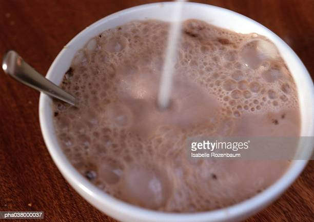 Chocolate milk in bowl, with spoon, liquid being poured into bowl, blurred