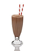Classic glass of chocolate milkshake standing on reflective white backdrop. There are two old-fashioned red-and-white straws standing in the glass. Visible reflection of the glass on the foreground.