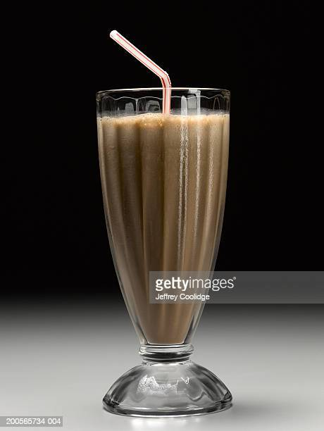 Chocolate milkshake with drinking straw, close-up