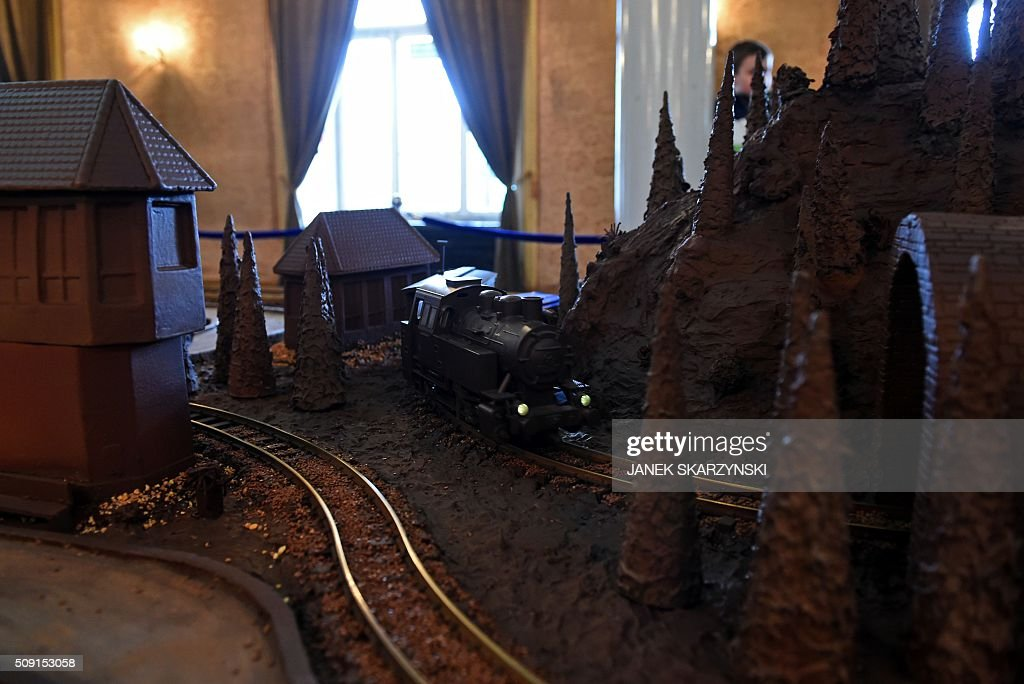 A chocolate mock-up of a train drives through a landscape made out of chocolate at the Warsaw Railway Museum on February 9, 2016 in Warsaw. Five hundred kilograms of chocolate were used to make the model. Everything is edible, besides the tracks and the engine. / AFP / JANEK SKARZYNSKI