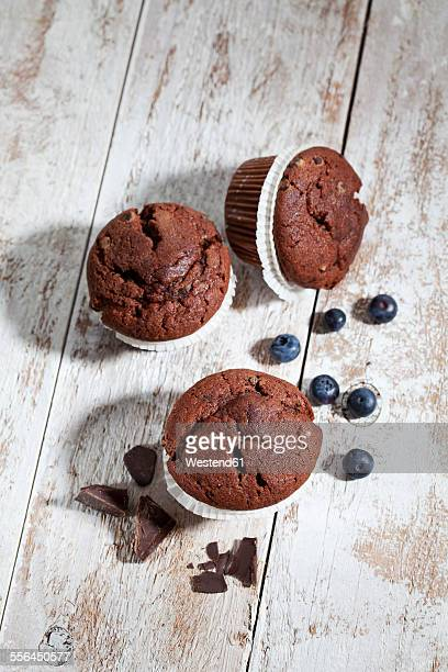 Chocolate muffins and blueberries on wood