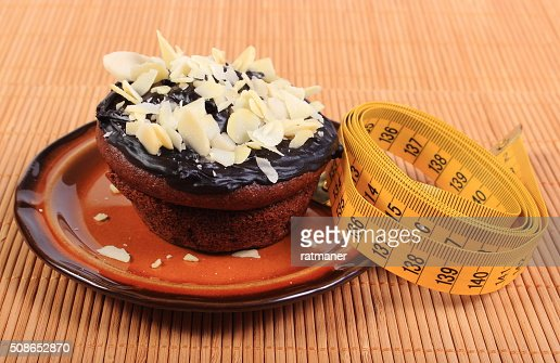 Chocolate muffins with almonds and tape measure : Stock Photo