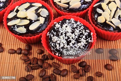 Chocolate muffins with desiccated coconut and almonds, coffee grains : Stock Photo