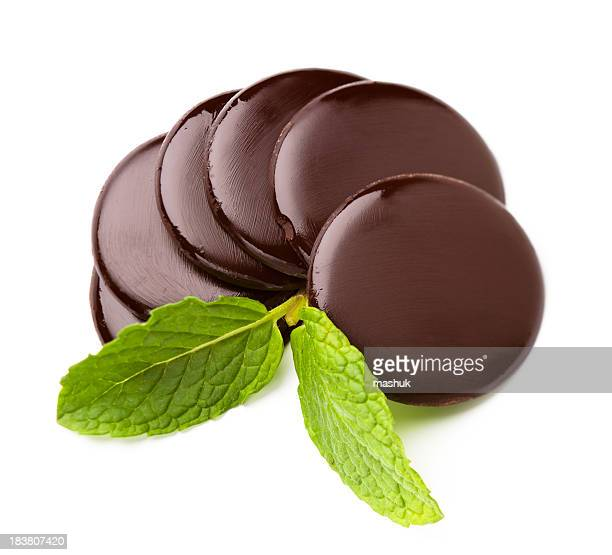 Chocolate rounds with mint leaf on white background