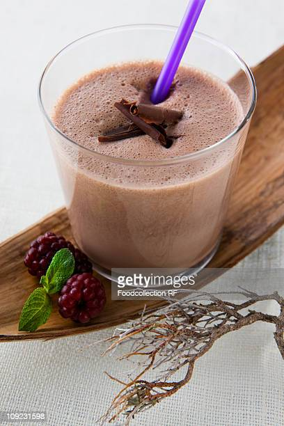 Chocolate shake and blackberries on wooden tray, close-up