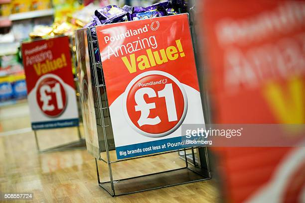 Chocolate snacks sit in a wire basket bin with a one pound sterling sign attached at Poundland Group Plc store in Leigh UK on Thursday Feb 4 2016 UK...