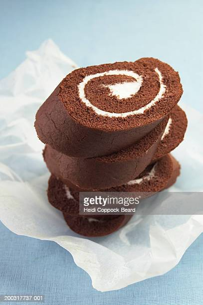 Chocolate swiss rolls on paper, close-up