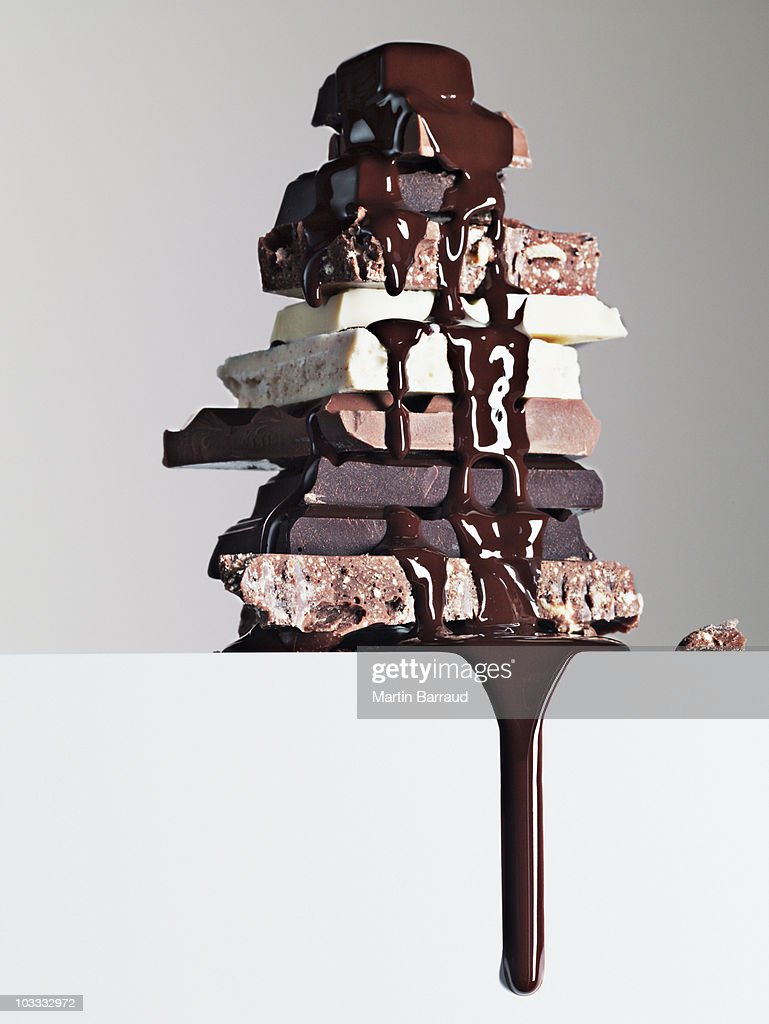 Chocolate syrup dripping over stack of chocolate bars : Stock Photo