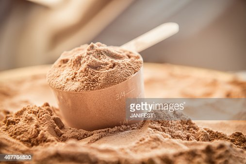 Chocolate whey protein powder with a filled scoop : Stock Photo