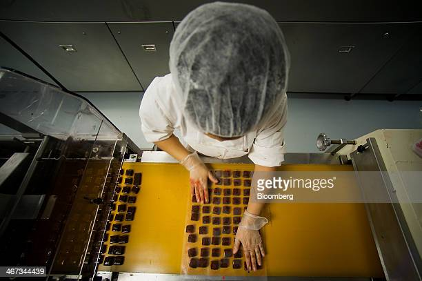 Chocolates come out of a machine after receiving a coating at the Jacques Torres Chocolate factory in the Brooklyn borough of New York US on Thursday...