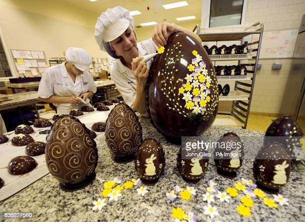 Chocolatier Josie Raine puts the finishing touches with handmade icing spring flowers to an Imperial Easter Egg at Bettys in Harrogate North Yorkshire