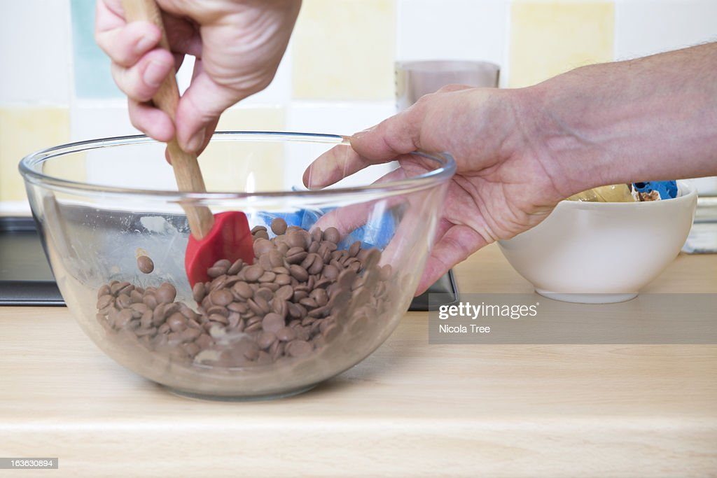 A chocolatier mixing milk chocolate in a bowl : Stock Photo
