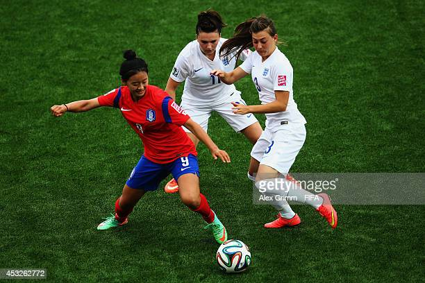 Choe Yuri of Korea Republic is challenged by Melissa Lawley and Hannah Blundell of England during the FIFA U20 Women's World Cup Canada 2014 group C...