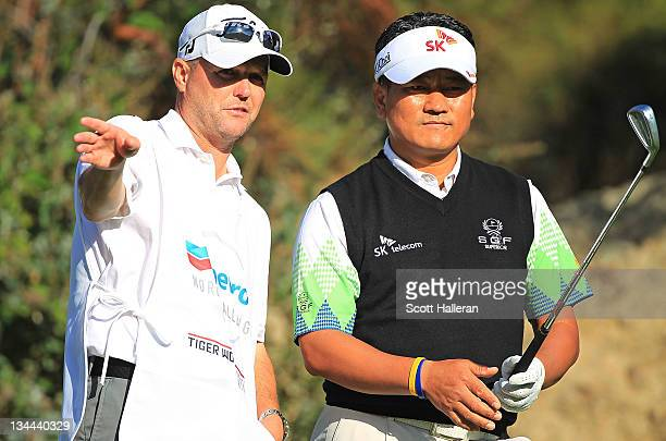 J Choi of South Korea chats with his caddie Steve Underwood on the 15th hole during the first round of the Chevron World Challenge at Sherwood...