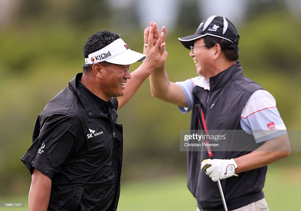 K.J. Choi (L) of South Korea high-fives an amateur after a made putt on the ninth hole green during the Pro-Am round of the Hyundai Tournament of Champions at the Plantation Course on January 3, 2013 in Kapalua, Hawaii.