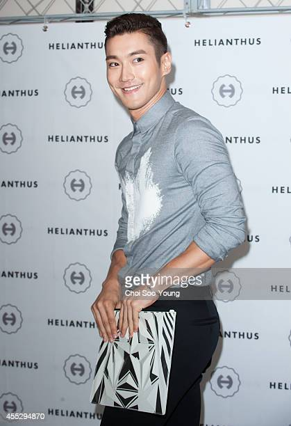 Choi SiWon of Super Junior poses for photographs during the Choi SiWon and HELIANTHUS collaboration event at Lotte Duty Free on September 1 2014 in...