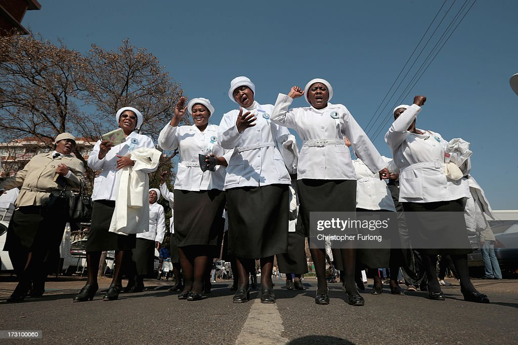 A choir from the Mabopane United Congregation Church sing and pray as people gather to pay tribute to Former South African President Nelson Mandela at the memorial wall at the Medi-Clinic Heart Hospital on July 7, 2013 in Pretoria, South Africa. Mandela has been hospitalized at the Medi-Clinic Hospital since June 8 for treatment for a recurring lung infection.