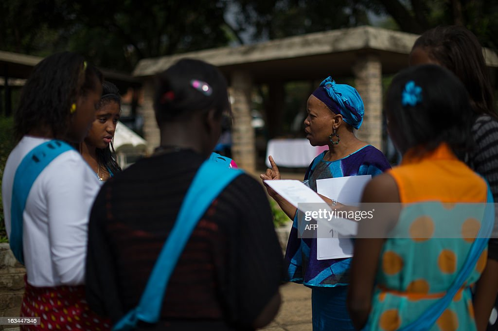 A choir leader coaches girls outside a church during mass at the Consolata church in Nairobi's Westlands neighbourhood on March 10, 2013. Kenyans called Sunday for reconciliation between the winning and losing camps in the presidential poll, a day after Uhuru Kenyatta, who faces an international trial for crimes against humanity, was declared the winner but his chief rival refused to concede.