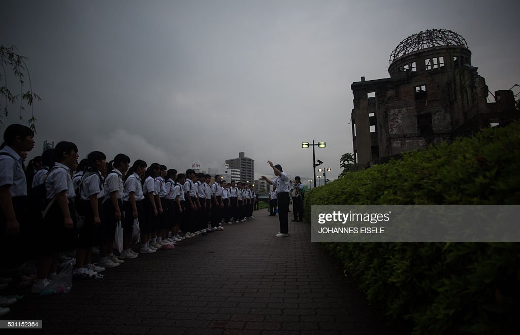 A choir signs in front of the Peace Memorial Genbaku Dome in the Hiroshima Peace Memorial park in Naka Ward, Hiroshima Prefecture on May 25, 2016. US President Barack Obama is set to become the first sitting US president to visit Hiroshima when he journeys on May 27 with Japanese Prime Minister Shinzo Abe, hallowed ground to Japanese but, for more than 70 years, a no-go zone for 11 of his Oval Office predecessors. / AFP / JOHANNES