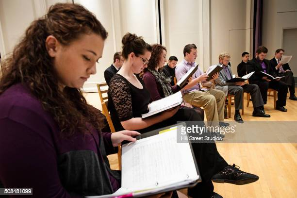 Choir singers reading sheet music on stage
