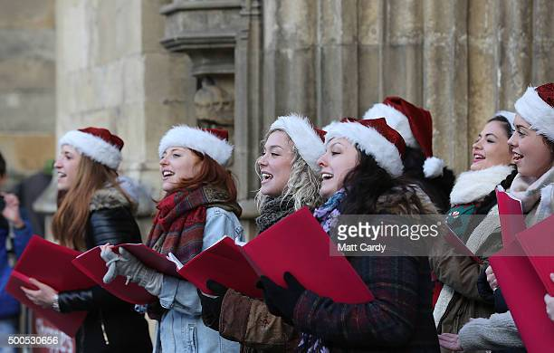A choir sings as shoppers browse stalls at the traditional Christmas market close to the historic Roman Baths and Bath Abbey on December 8 2015 in...
