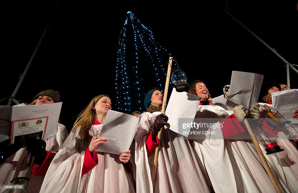 A choir sings christmas carols during the official ceremony to turn on the Christmas tree lights in Trafalgar Square central London on December 6...