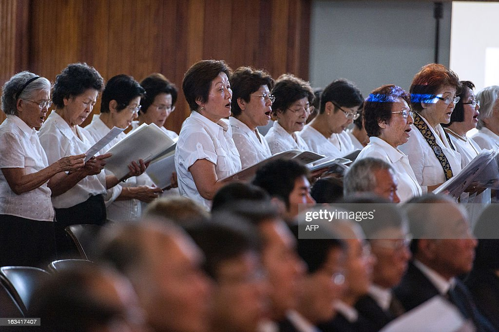A choir sings during a memorial service for the victims of the earthquake and tsunami of March 11, 2011 in Japan, at the Brazilian Society of Japanese Culture and Social Welfare in Sao Paulo, Brazil on March 9, 2013. Japan will commemorate the second anniversary of a 9.0 magnitude offshore earthquake and giant tsunami that killed 15,880 people and left 2,694 unaccounted for, mainly in the Pacific coastline of the Tohoku region in the nation's northeast.