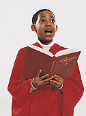 Choirboy in a Red Gown Singing From a Hymn Book