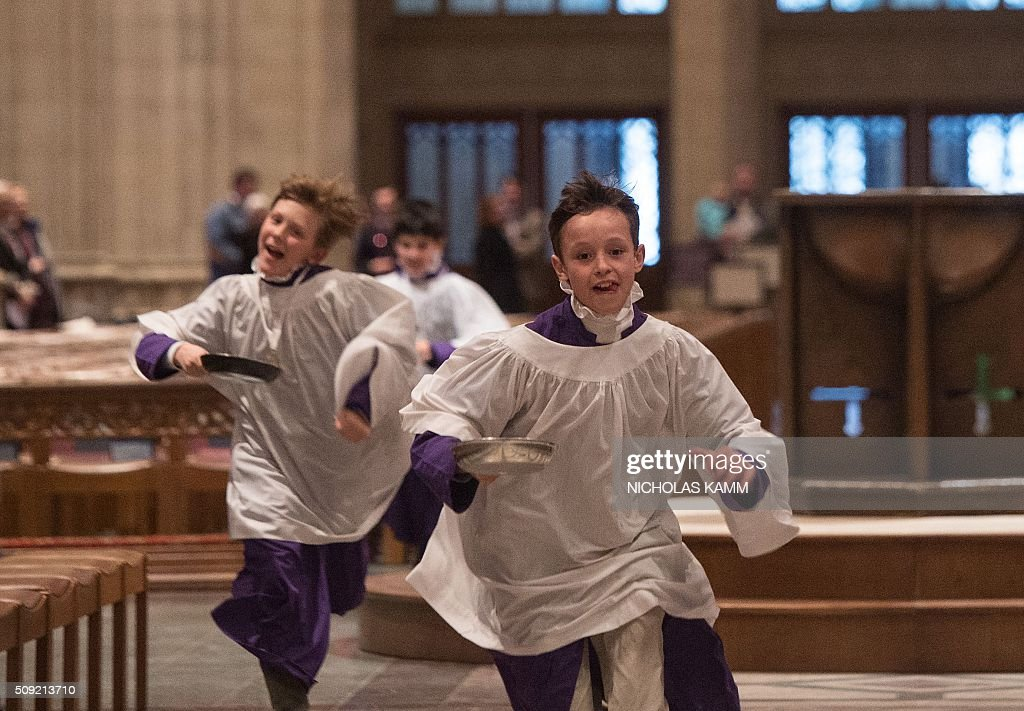 Choirboys take part in the Shrove Tuesday Pancake Race at the National Cathedral in Washington, DC, on February 9, 2016. Shrove Tuesday, also known as Mardi Gras, precedes Ash Wednesday, the first day of Lent. / AFP / Nicholas Kamm