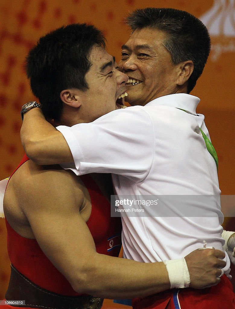 Chol Kum Pang of Korea celebrates with his coach after winning the Men's Weightlifting 77kg competition during day four of the 16th Asian Games Guangzhou 2010 at Dongguan Gymnasium on November 16, 2010 in Guangzhou, China.