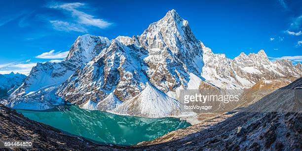 Cholatse dramatic mountain peak towering over glacial lake Khumbu Himalayas