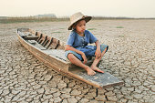 Children sitting on wooden boat at cracked land. Metaphor for Global warming and Climate change.