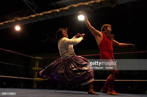 Cholita Yolanda La Amorosa fighting with Barba Negra during the 'Titans of the Ring' wrestling group performance at El Alto's Multifunctional Centre...